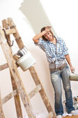 Home improvement: Cheerful woman with paint roller — Stock Photo