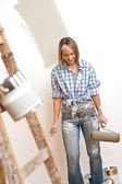 Home improvement: Young woman with paint roller and ladder — Stock Photo
