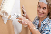 Home improvement: Young woman painting wall — Stock Photo