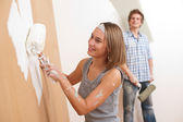Home improvement: Young man and woman painting wall — Stock Photo