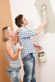 Home improvement: Man painting wall with paintbrush — Stock Photo