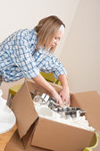 Moving house: Woman unpacking box with pot — Stock Photo