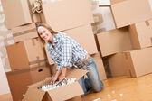 Moving house: Happy woman unpacking box — Stock Photo