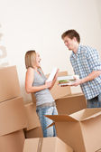 Moving house: Young couple with box in new home — Stock Photo