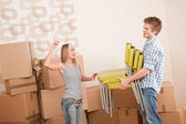 Moving house: Man and woman with box and chair — Stock Photo