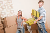 Moving house: Young couple with box and chair — Stock Photo