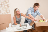 Moving house: Young couple unpacking kitchen dishes — Stock Photo