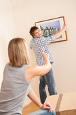 Moving house: Couple hanging picture on wall — Stockfoto