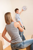 Moving house: Young couple hanging clock on wall — Stock Photo