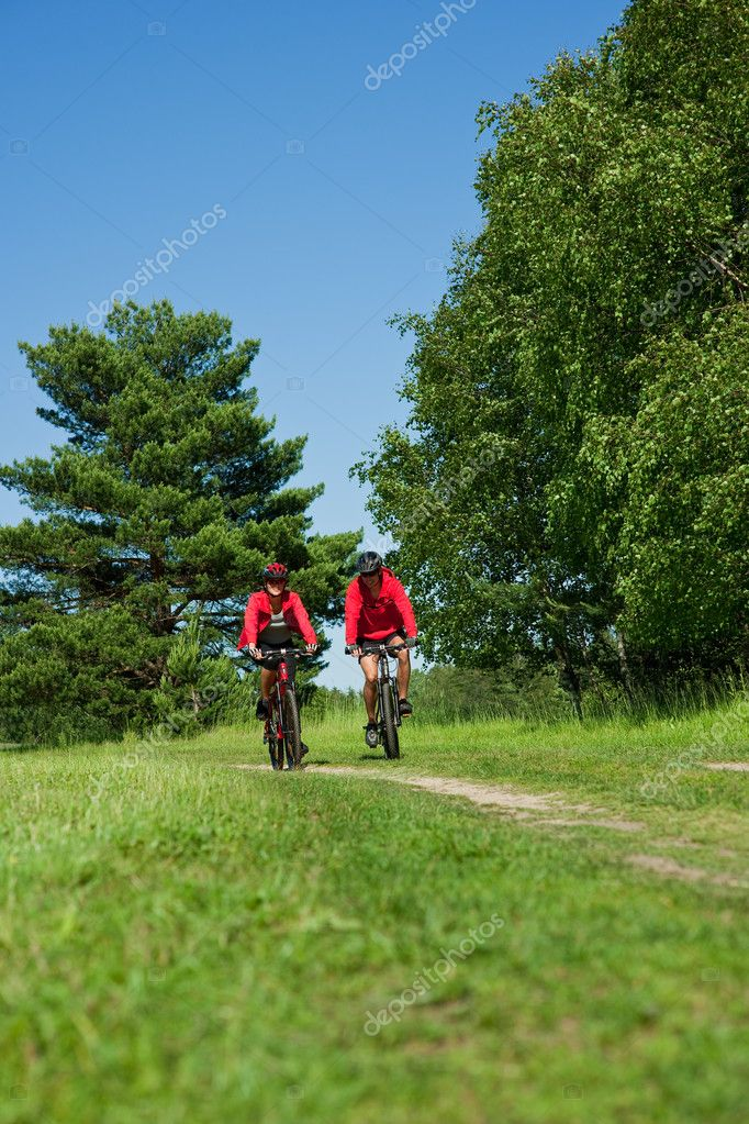Young couple with mountine bike in spring nature on sunny day biking — Stock Photo #4690730
