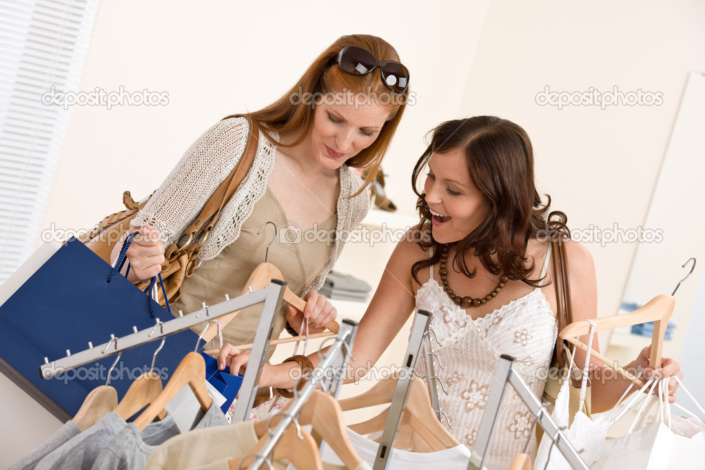 Fashion shopping -  Two happy young woman choose clothes in shop holding shopping bag — Stock Photo #4691322