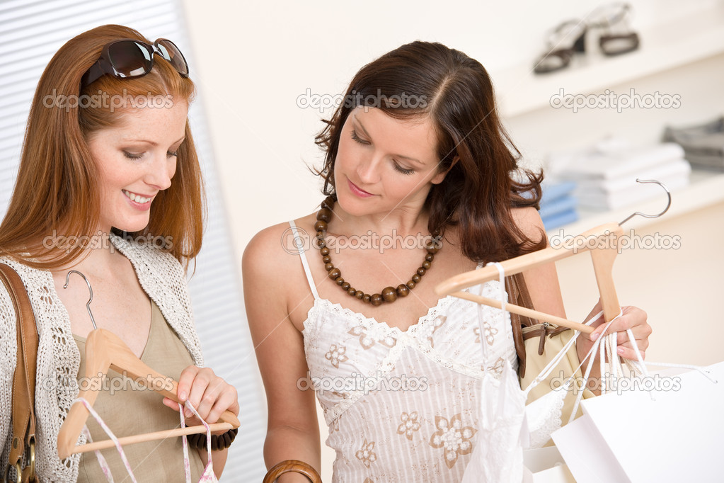 Fashion shopping -  Two happy young woman choose clothes in shop holding shopping bag — Stock Photo #4691337