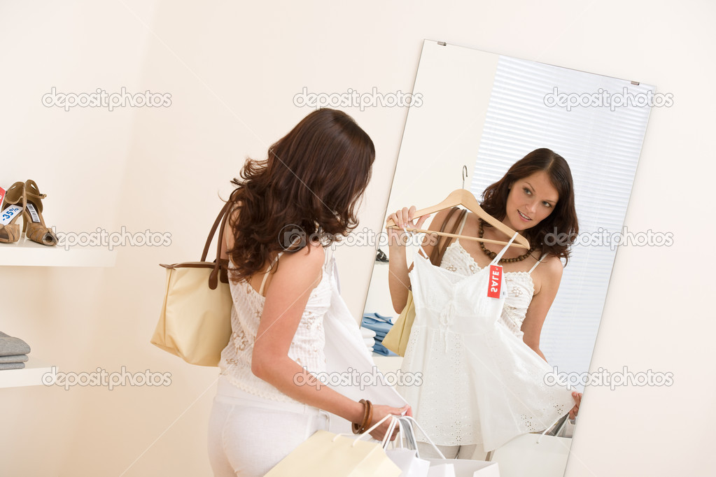 Fashion shopping: Happy woman choose sale clothes, holding shopping bag in mirror — Stock Photo #4691350