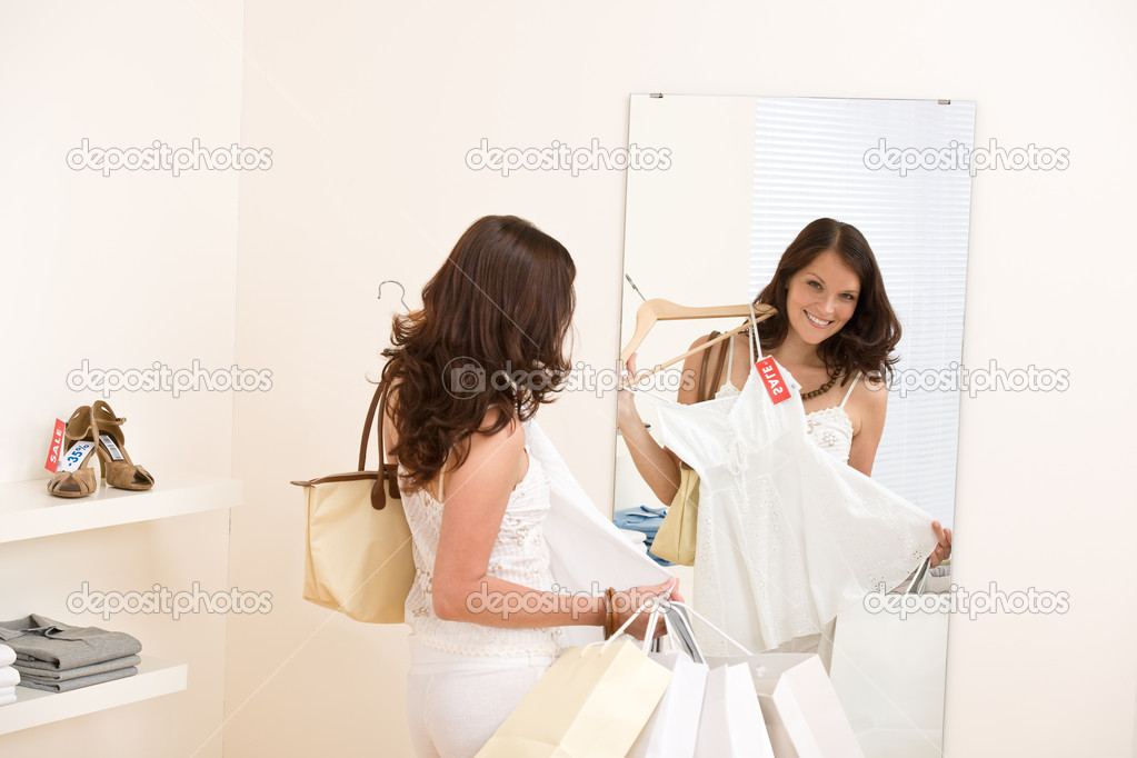 Fashion shopping - Happy woman choose sale clothes, holding shopping bag in mirror — Stock Photo #4691352