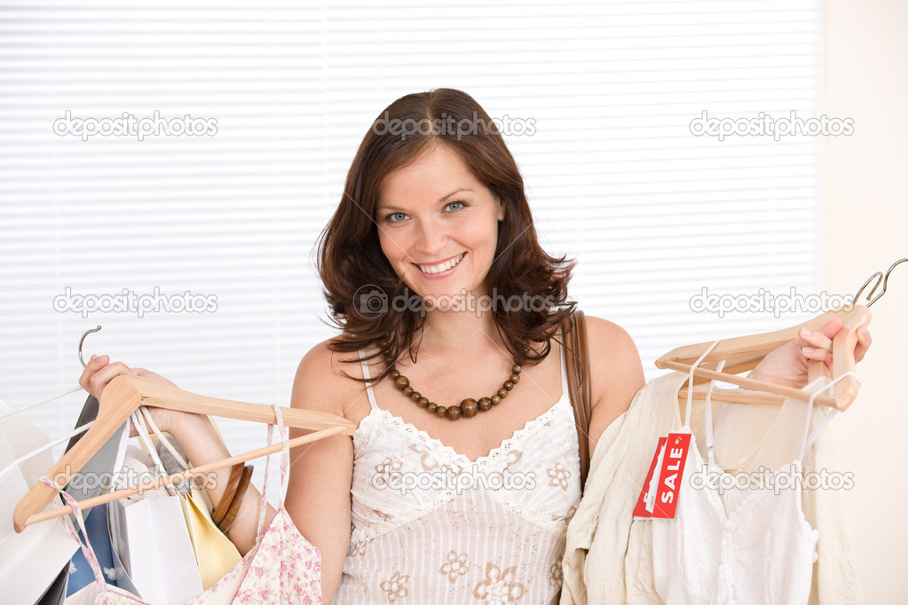 Fashion shopping - Happy woman choose sale clothes, holding shopping bag — Stockfoto #4691356