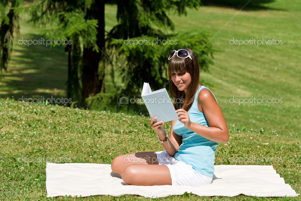 Smiling young woman read book in park on sunny day sitting on blanket  Stock Photo #4692091