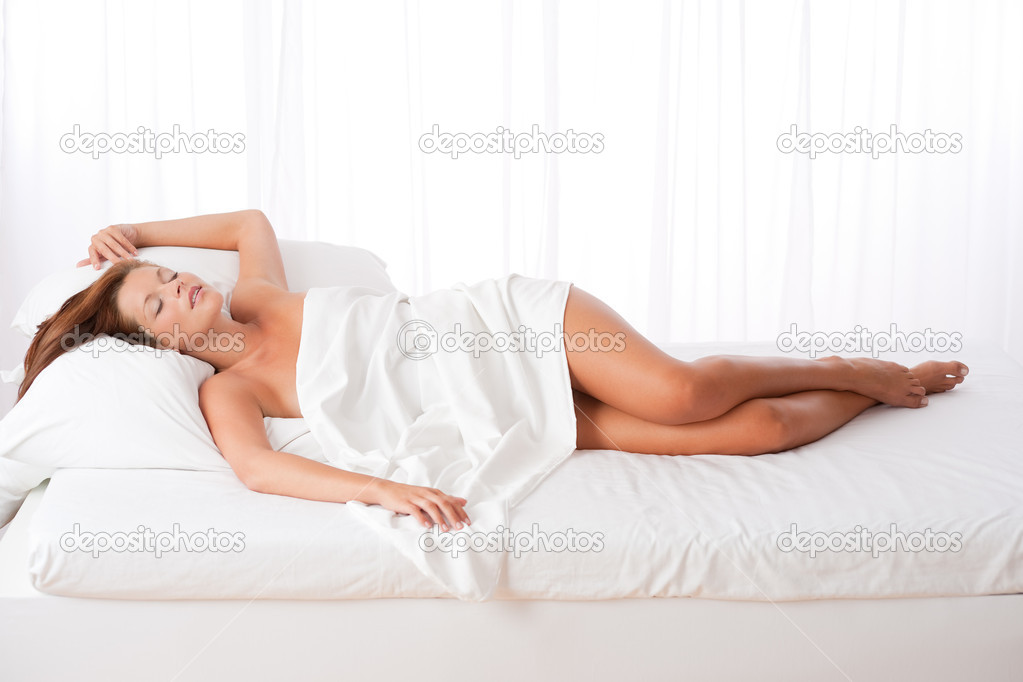 Long shot of woman lying in bed in bedroom  Stok fotoraf #4692689