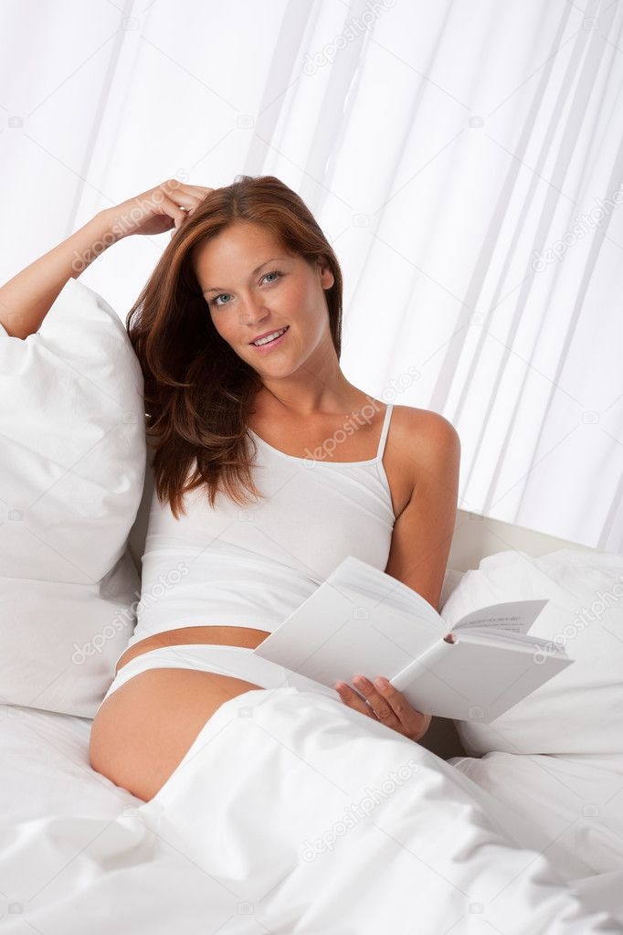 Young woman holding white book sitting in bed  Stock Photo #4692803