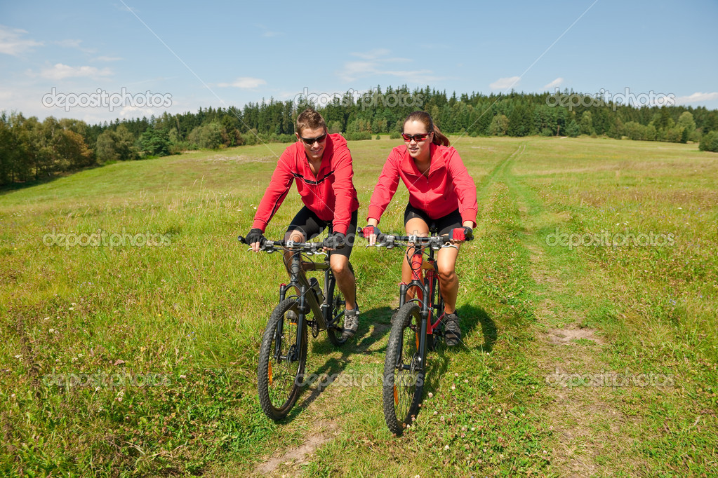 Young couple riding mountain bike in spring meadow nature on sunny day — Stock Photo #4693585
