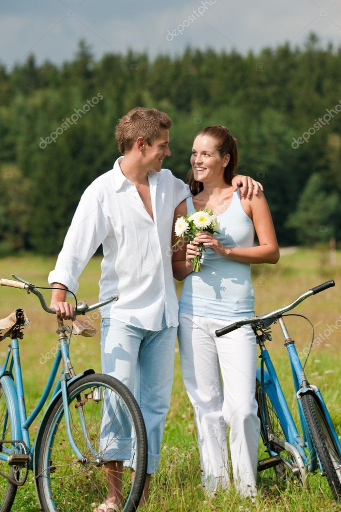 Romantic young couple walking with old bike in meadow on sunny day  Stock Photo #4693596