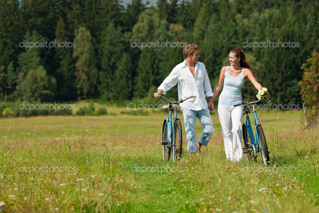Romantic young couple with old bike in spring nature on sunny day — Stock Photo #4693619