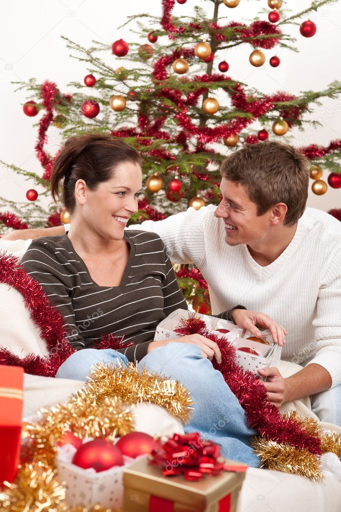 Smiling young couple sitting together in front of Christmas tree  Stock Photo #4696032