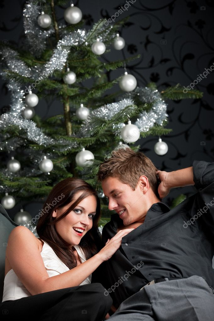 Extravagant man and woman in front of Christmas tree and black wallpaper — Stock Photo #4696050