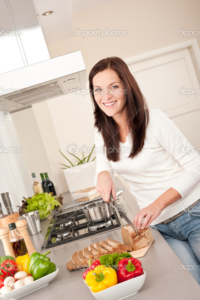 Smiling woman cutting bread in the kitchen — Stock Photo #4696344