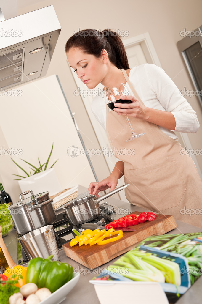 Young woman cooking in the kitchen and holding glass of red wine  Stock Photo #4696365