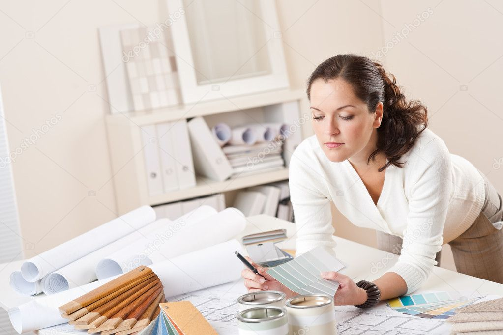 Young female interior designer working at office with color swatch and can of paint — Foto Stock #4698418