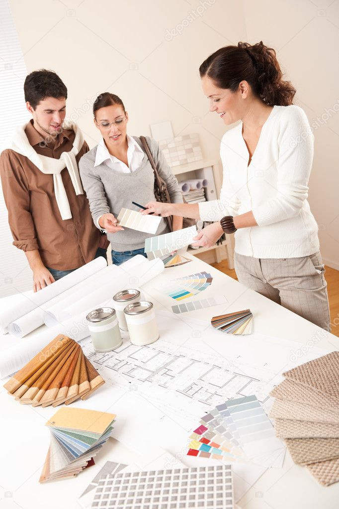 Female Interior Designer With Two Clients At Office