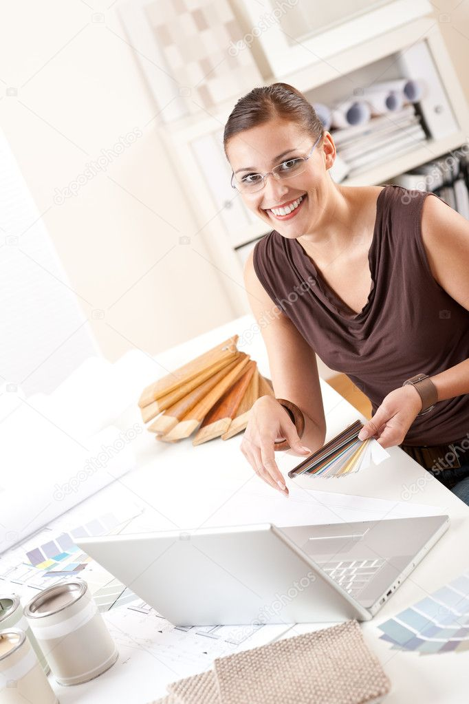 Smiling female designer with color swatch and laptop at office  Stock Photo #4698475