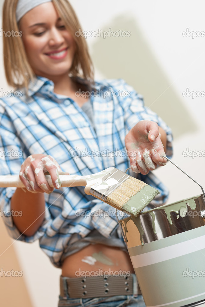 Home improvement: Smiling woman holding paint can and brush  Stock Photo #4698786