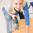 Home improvement - handywoman cutting wooden floor — Stock Photo