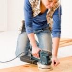 Home improvement - handywoman sanding wooden floor — Stock Photo #4946846