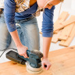 Home improvement - handywoman sanding wooden floor — Stockfoto