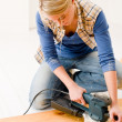 Stock Photo: Home improvement - handywoman sanding wooden floor