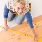 Home improvement - handywoman installing wooden floor — Stock Photo