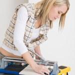 Home improvement - handywoman cutting tile — Stock Photo
