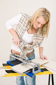 Home improvement - handywoman cutting tile — Stock Photo