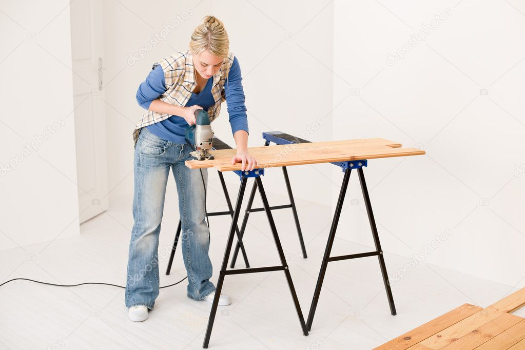Home improvement - handywoman cutting wooden floor  with jigsaw  Stock Photo #4946831