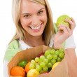 Stock Photo: Healthy lifestyle - cheerful woman with fruit shopping bag