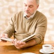 Senior mature man reading book having coffee — Stock Photo