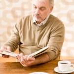 Senior mature man reading book having coffee — Stock Photo
