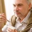 Senior mature man eat yogurt snack - Foto de Stock  