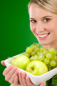Healthy lifestyle - woman holding bowl with green fruit — Stock Photo
