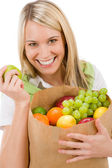 Healthy lifestyle - cheerful woman with fruit shopping bag — Stock Photo