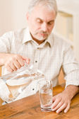 Senior mature man pour water sitting at table — Stock Photo