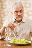 Senior mature man eat healthy salad and white wine — Stock Photo