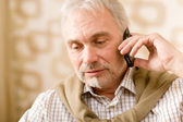 Thoughtful senior mature man with mobile phone — Stock Photo